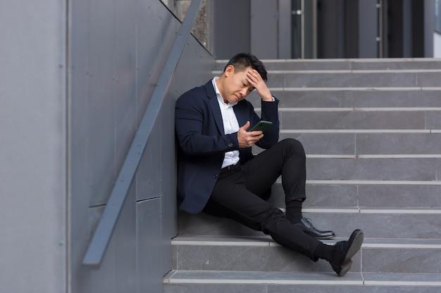 Aziatische zakenman leest slecht nieuws van de telefoon, zit in de buurt van het kantoor op de trap, depressief, hoop te verliezen