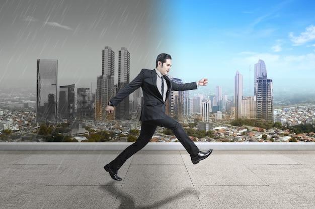 Aziatische zakenman loopt naar verschillende klimaten met stadsgezichten achtergrond