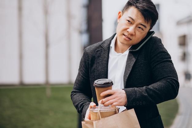 Aziatische zakenman met afhaalmaaltijden, praten over de telefoon