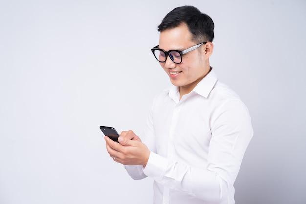 Aziatische zakenman met behulp van smartphone op wit