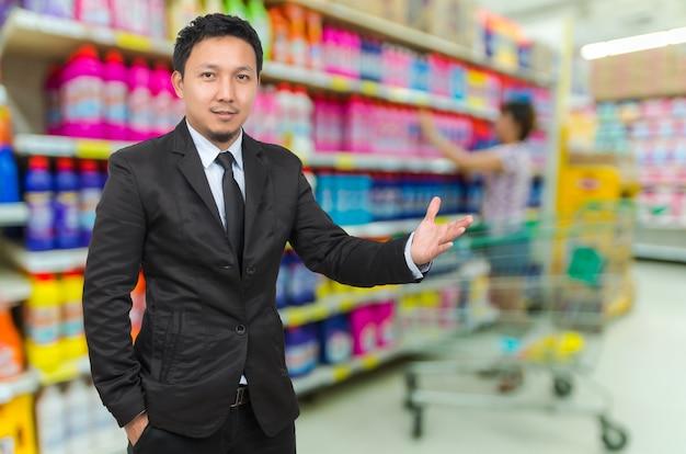 Aziatische zakenman met gastvrije gebaar op supermarkt vervagen achtergrond
