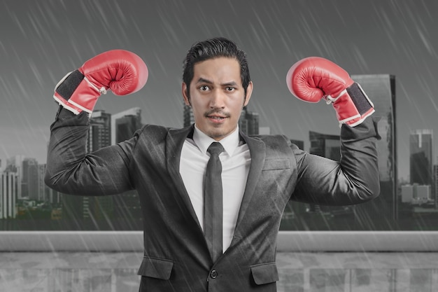 Aziatische zakenman met rode bokshandschoenen met regenachtige achtergrond