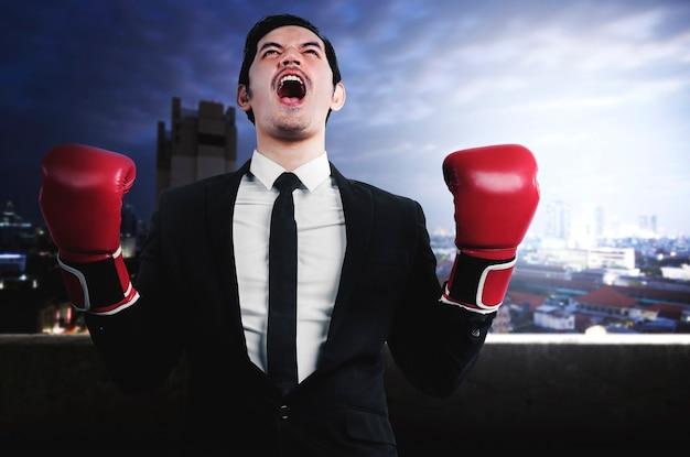 Aziatische zakenman met rode bokshandschoenen met stadsgezichtenachtergrond