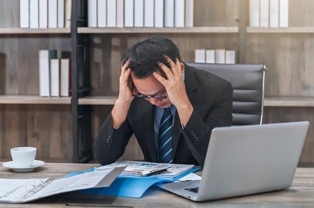Aziatische zakenman met stress en hoofdpijn die op kantoor werkt