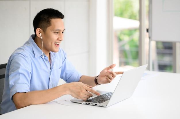 Aziatische zakenman met videoconferentiegesprek met collega via laptop