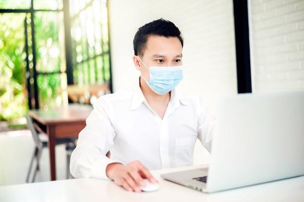 Aziatische zakenman met zwart haar dragen van een gezichtsmasker voor covid 19 bescherming corona griep op modern kantoor, hij werkt met laptop tussen seizoensgebonden virale ziekten.