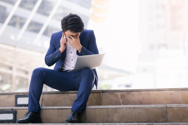 Aziatische zakenman mislukken en serieus werk op telefoon en laptop in de stad