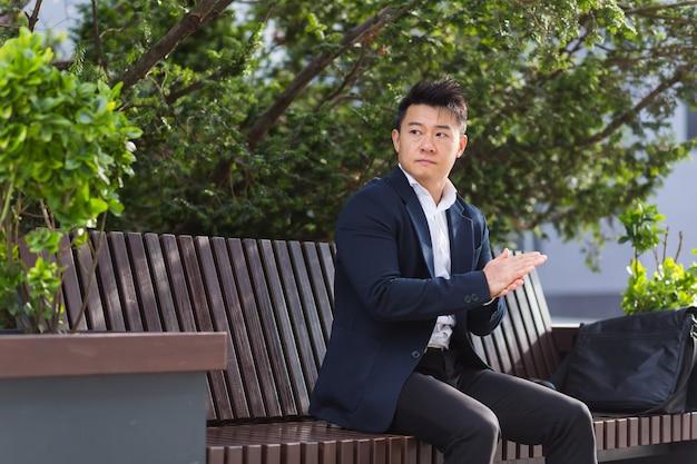 Aziatische zakenman moe na het werk, zittend op een bankje met vermoeidheid en hoofdpijn, heeft stress en paniekaanvallen