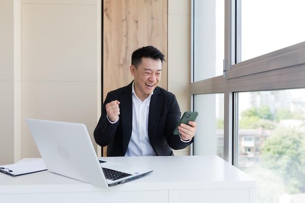 Aziatische zakenman op kantoor die naar mobiele telefoon kijkt met emotiewinnaar of win or