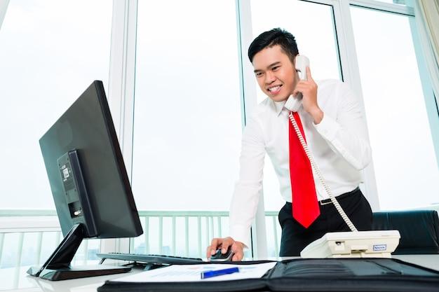 Aziatische zakenman op telefoon die in bureau op computer werkt