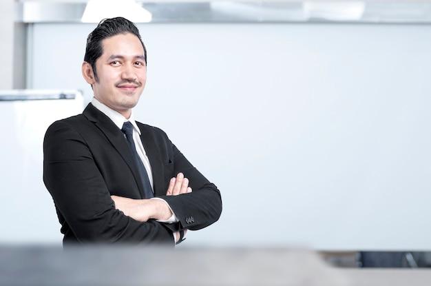 Aziatische zakenman permanent met gekruiste armen op de kantoorruimte