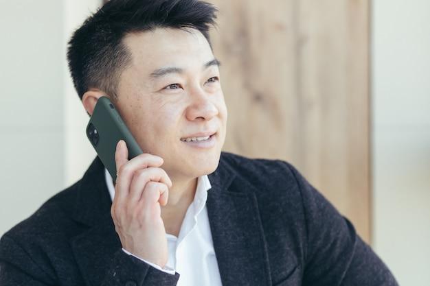 Aziatische zakenman portret succesvol en gelukkig lachend praten aan de telefoon in een pak