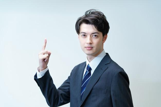 Aziatische zakenman poseren met zijn wijsvinger omhoog