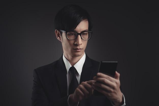 Aziatische zakenman scant gezicht door slimme telefoon met behulp van gezichtsherkenningssysteem.