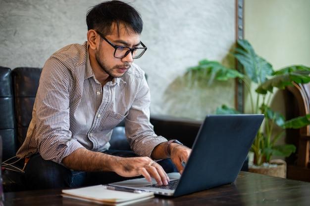 Aziatische zakenman typen op laptop en werken in kantoor aan huis