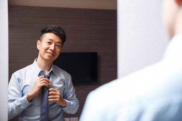 Aziatische zakenman verkleedt zich in zijn huis, hij gaat 's ochtends een interview krijgen.