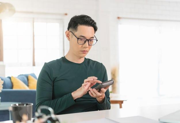 Aziatische zakenmanaccountant die calculator gebruikt om bedrijfsgegevens thuis te berekenen.