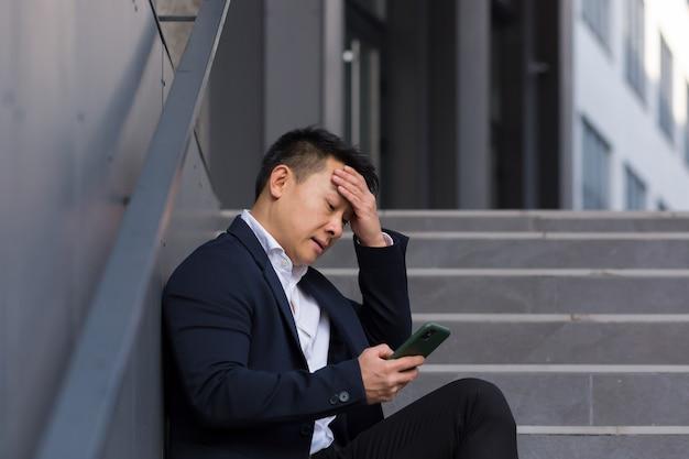 Aziatische zakenmanmakelaar meldt slecht nieuws terwijl hij aan de telefoon praat, in de buurt van kantoor op de trap zit, depressief de hoop verliest en zijn baan failliet gaat