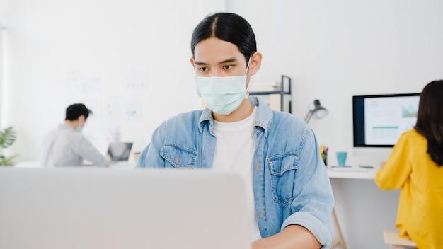 Aziatische zakenmanondernemer die medisch gezichtsmasker draagt voor sociale afstand in een nieuwe normale situatie voor viruspreventie tijdens het gebruik van laptop weer op het werk op kantoor. levensstijl na coronavirus.