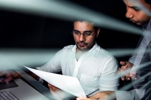 Aziatische zakenmanteam werkende nachtdienst die project bespreekt