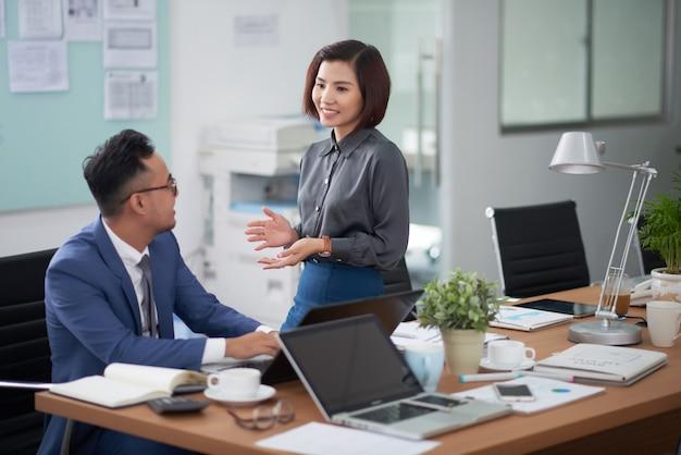 Aziatische zakenmanzitting bij vergaderingslijst en het spreken aan vrouwelijke collega