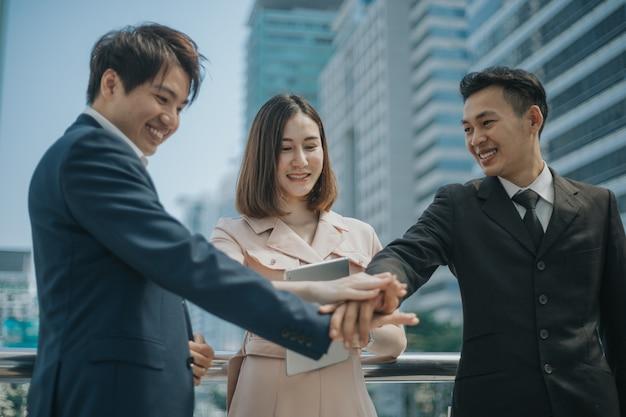 Aziatische zakenmensen die de handen ineen slaan.
