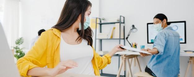 Aziatische zakenmensen dragen een gezichtsmasker voor sociale afstand in een nieuwe normale situatie voor viruspreventie en het doorgeven van documenten met afstand houden op kantoor. leefstijl en werk na coronavirus.