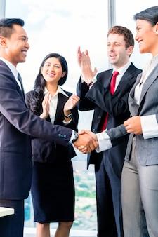Aziatische zakenmensen handen schudden