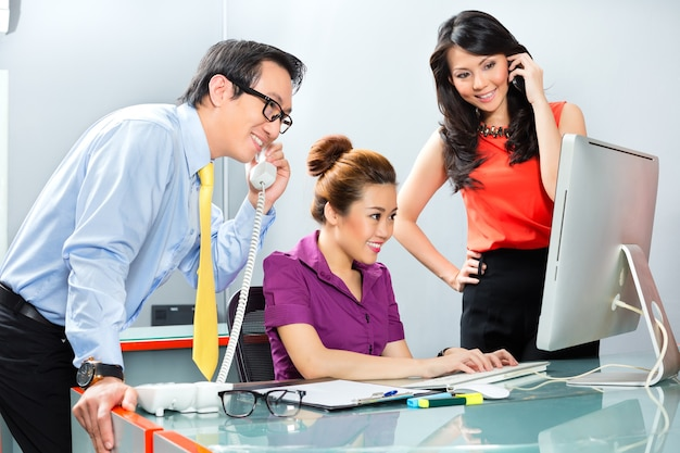 Aziatische zakenmensen in een kantoor werken als een team samen voor succes in een gezamenlijk project