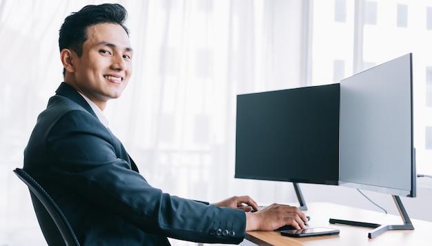 Aziatische zakenmensen zijn gefocust op werken. een computer met twee lege schermen