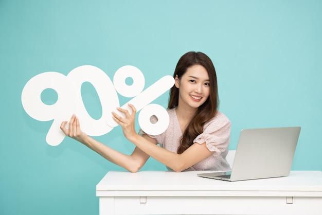 Aziatische zakenvrouw die 90 nummer toont en vasthoudt en met laptop zit