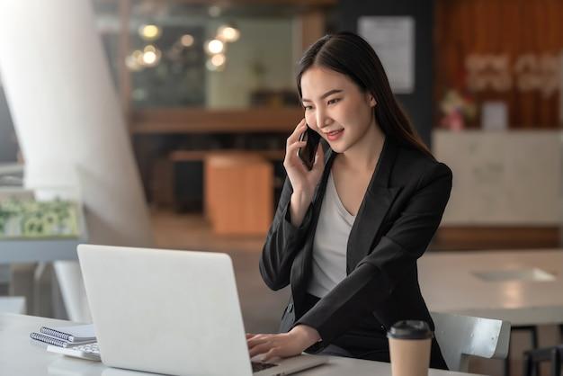 Aziatische zakenvrouw die aan de telefoon praat met klanten die klaar zijn om een laptop op kantoor te gebruiken.