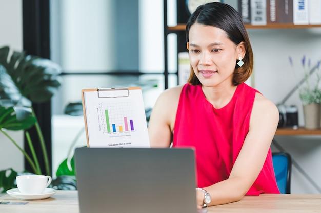 Aziatische zakenvrouw die bedrijfsrapport presenteert via videogesprek op een laptop thuis. ondernemer of ondernemer aan het werk, online winkelen, e-commerce, internetbankieren, thuiswerken concept