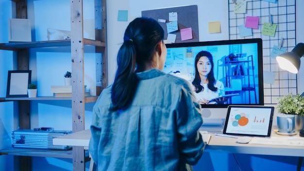 Aziatische zakenvrouw die desktop gebruikt, praat met collega's over het plan in een videogesprekvergadering in de woonkamer.