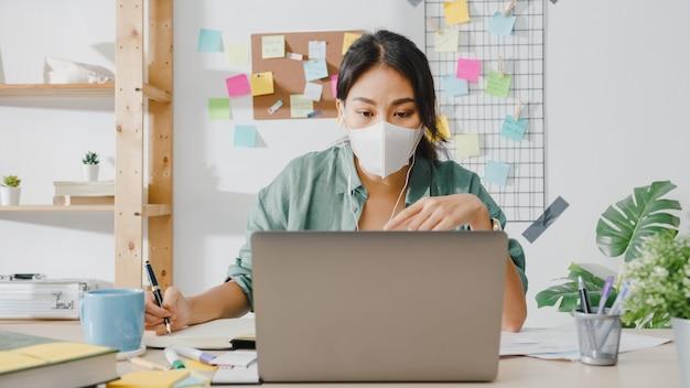 Aziatische zakenvrouw die een medisch gezichtsmasker draagt met behulp van een laptop praat met collega's over het plan in een videogesprek terwijl ze vanuit huis in de woonkamer werkt.