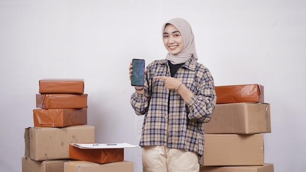 Aziatische zakenvrouw die het smartphonescherm toont dat op witte achtergrond wordt geïsoleerd