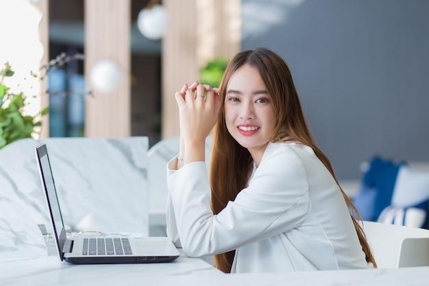 Aziatische zakenvrouw die in een co-werkruimte werkt met laptoppapierwerk (concept voor zakenvrouwen.)
