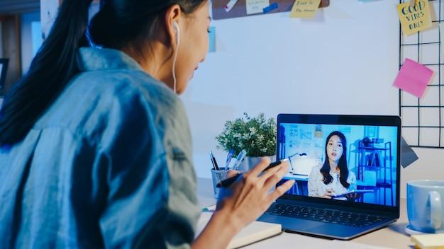 Aziatische zakenvrouw die laptop gebruikt, praat met collega's over het plan in een videogesprekvergadering in de woonkamer.