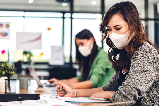 Aziatische zakenvrouw die laptop met gezichtsmasker gebruikt op kantoor