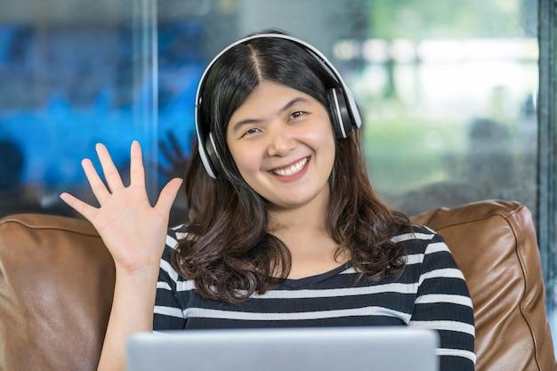 Aziatische zakenvrouw die met de hand zwaait om hallo te zeggen bij het maken van een videogesprek met een vriend
