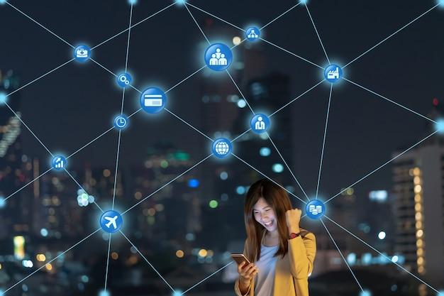 Aziatische zakenvrouw die slimme mobiele telefoon gebruikt voor de verbindingslijn van het computernetwerk