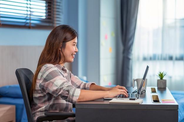 Aziatische zakenvrouw die technologielaptop gebruikt en van huis in binnenslaapkamer werkt