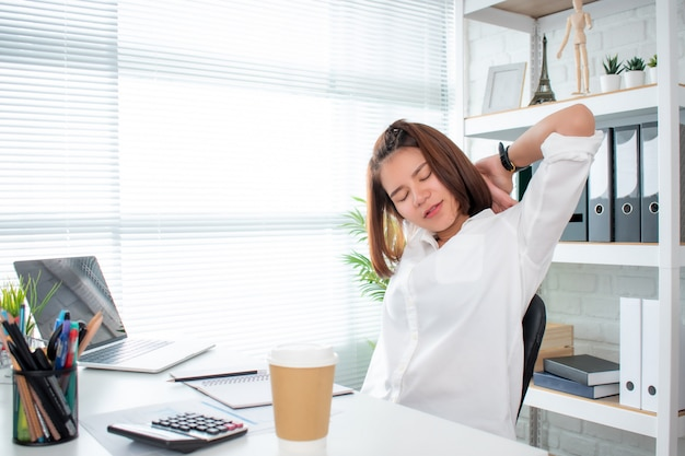 Aziatische zakenvrouw draagt een wit overhemd dat zich uitstrekt en voelt zich ontspannen aan de balie