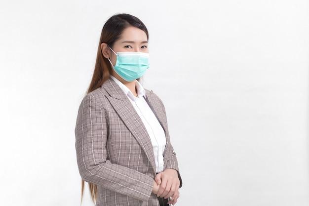Aziatische zakenvrouw draagt formeel pak en medisch gezichtsmasker om infectieziekte covid19 te beschermen