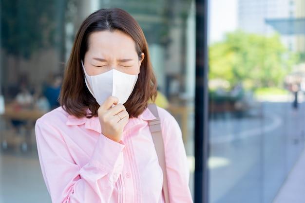Aziatische zakenvrouw draagt masker om stof en covid-19-virus te beschermen tijdens het wandelen buiten