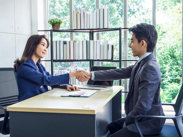 Aziatische zakenvrouw en zakenman dragen pak schudden handen in kantoor