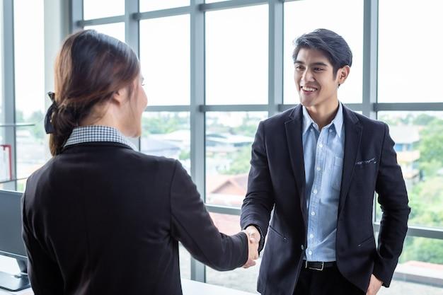 Aziatische zakenvrouw en zakenman handen schudden op in de kantoorruimte achtergrond nadat het contract is ondertekend of handdruk groet deal, bedrijf sprak vertrouwen aanmoedig en succesvol paar