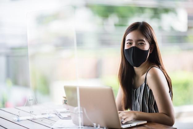 Aziatische zakenvrouw freelancer met chirurgisch gezichtsmasker, sociale afstand nemen van de nieuwe normale levensstijl na epidemie van coronavirus covid-19