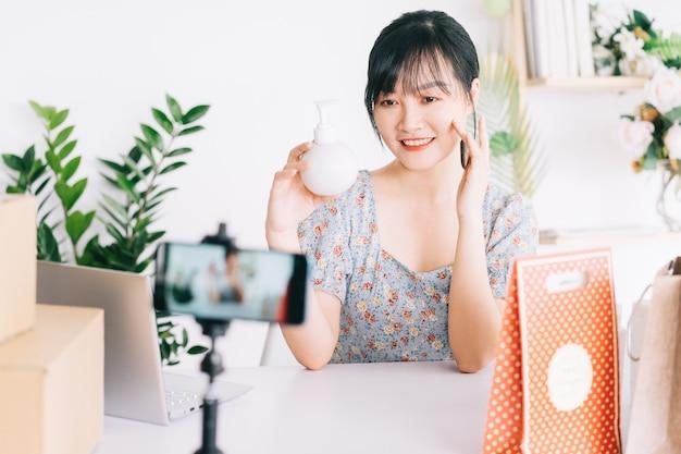 Aziatische zakenvrouw gebruikt smartphones om cosmetica live te streamen op sociale netwerksites en e-commerce sites.