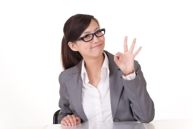 Aziatische zakenvrouw geeft je een ok gebaar, close-up portret op witte achtergrond.